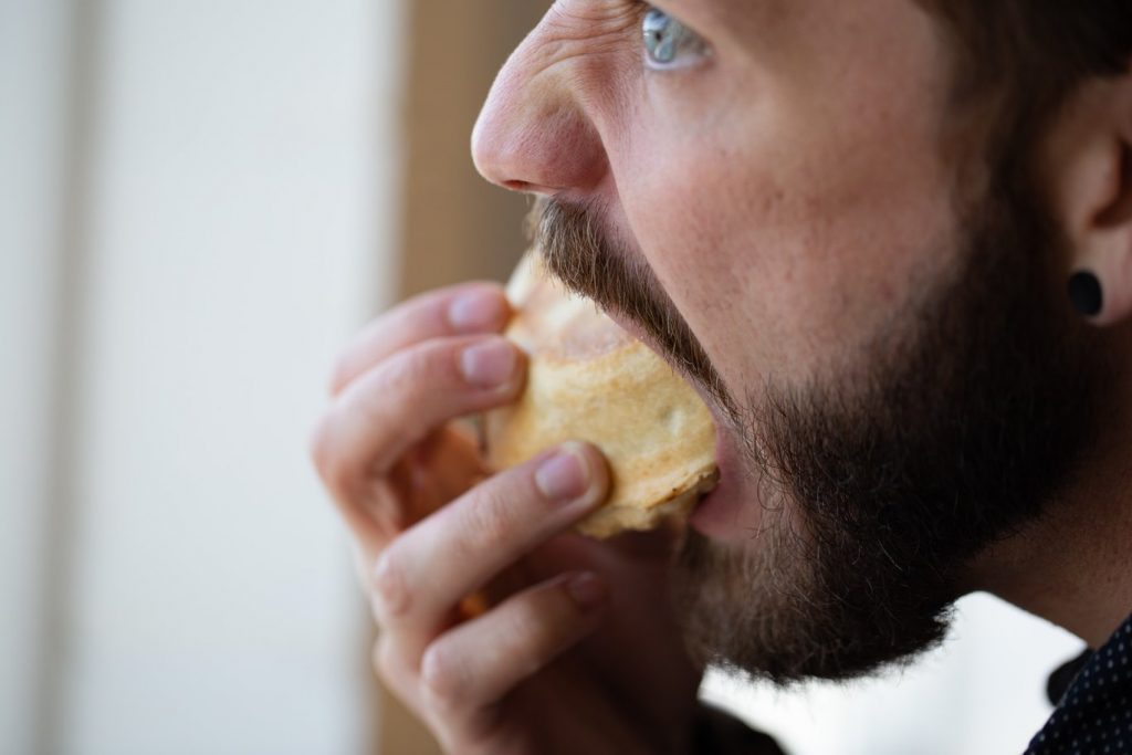 Man eating a muffin.