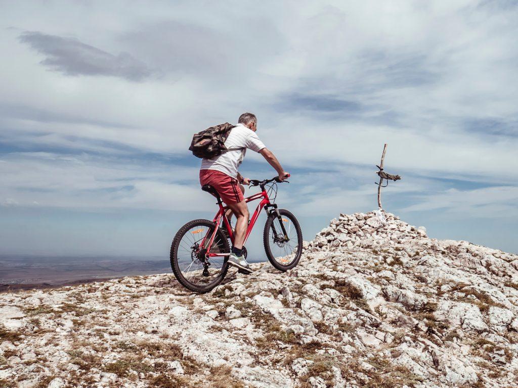 Man riding a bike in a hill.