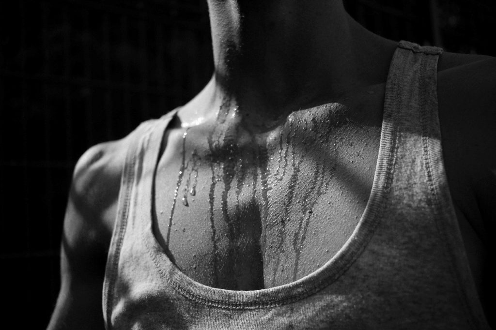 Sweaty man wearing a white tank top. Should you wash your tank tops every time?