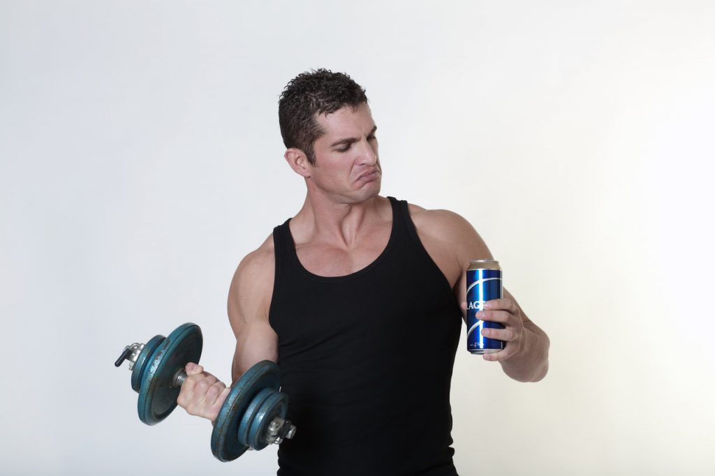 Man holding a dumbbell and a can of beer. Thinking about which one to do between alcohol and workouts.