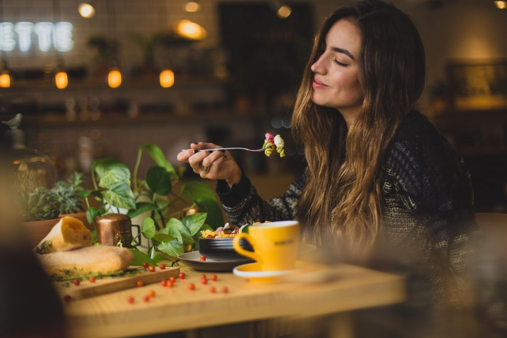 Women eating pasta at a table.