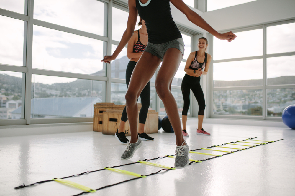 Woman training on agility ladder. This exercise shows a good example of physical fitness.