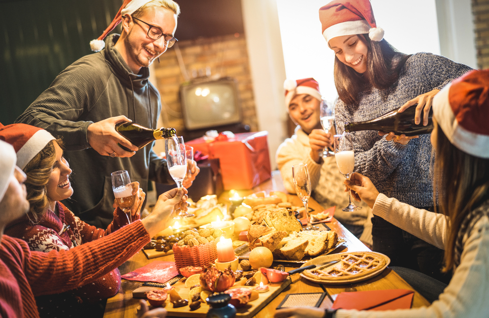 Friends group with Santa hats celebrating Christmas with champagne and sweets food at home dinner - Winter holidays concept with people enjoying time and having fun eating together. All the good food and sweets causes holiday weight gain.