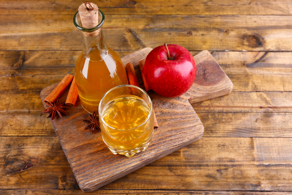 In the wooden background, Bragg's organic apple cider vinegar in glass bottle with cinnamon sticks and fresh apples on cutting board, on wooden background