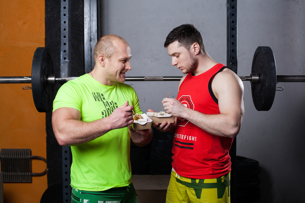 Two athletic men eating after workout to track their diet for weight loss.