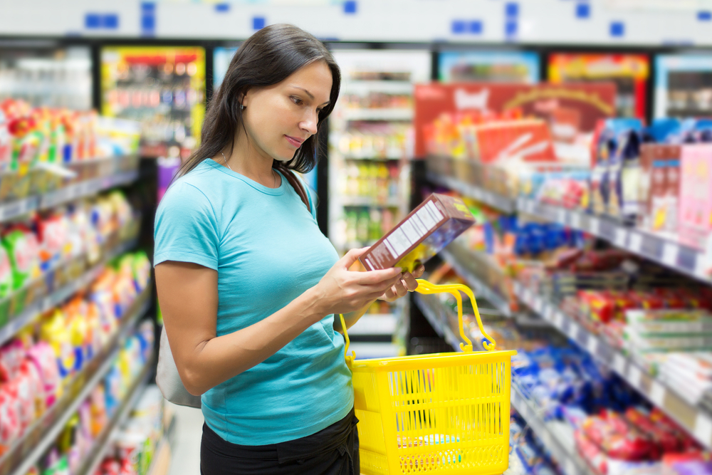 Woman reading food label in a grocery store aisle.