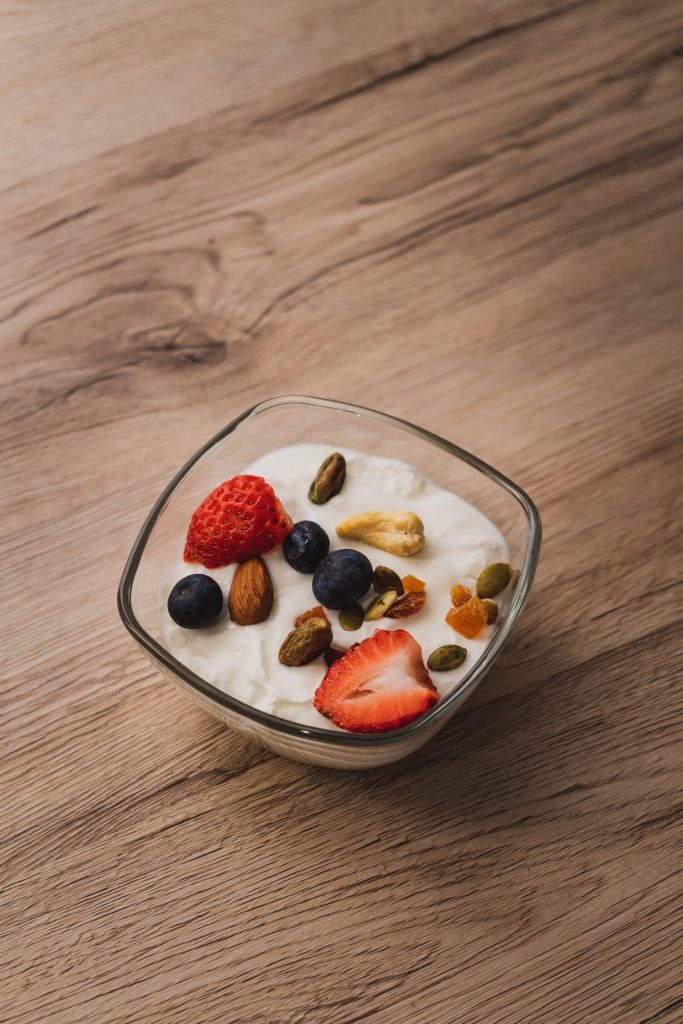 close up of a bowl of yogurt topped with berries and nuts
