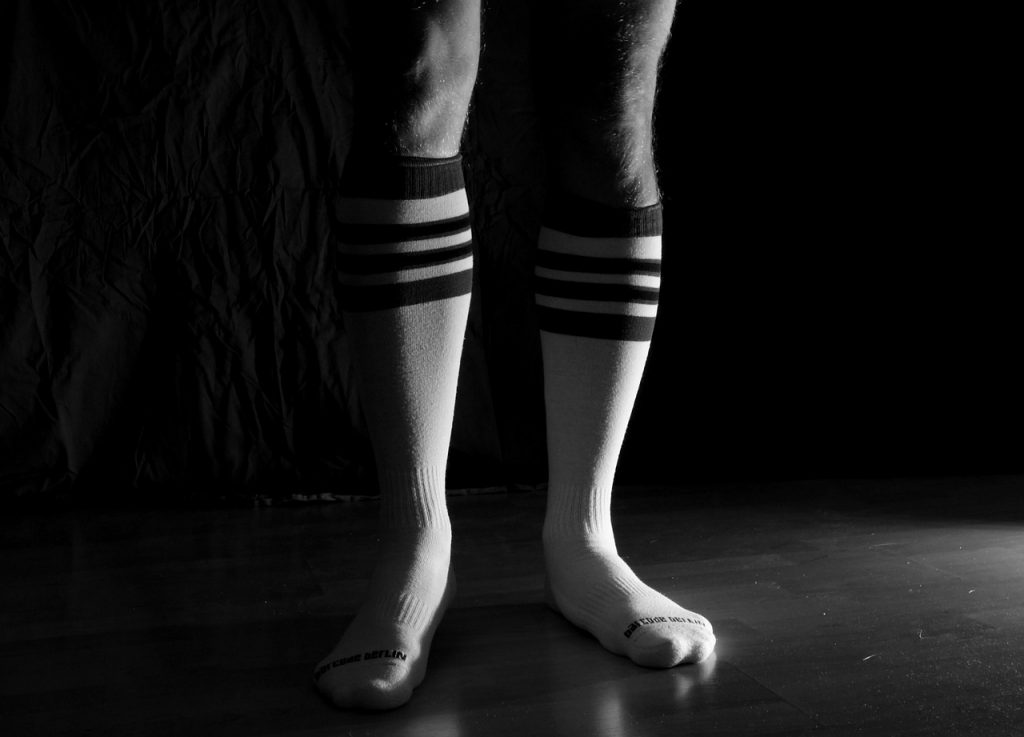 Man wearing sport socks in the dark. Should you wash your socks after every workout?