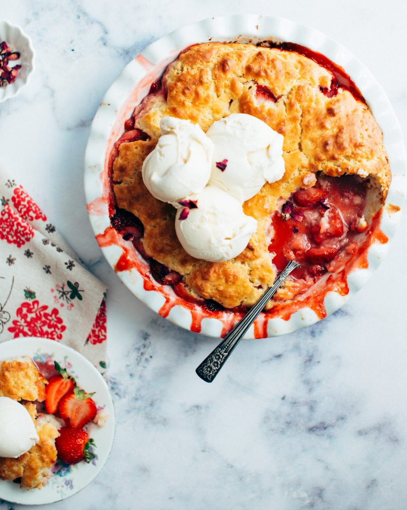 a bowl of vegetarian strawberry cobbler on a beautiful marble table