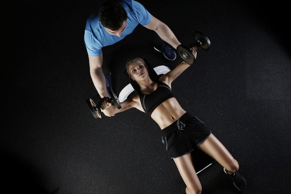 Woman doing strength training with a friend. This is a way to power through workout.