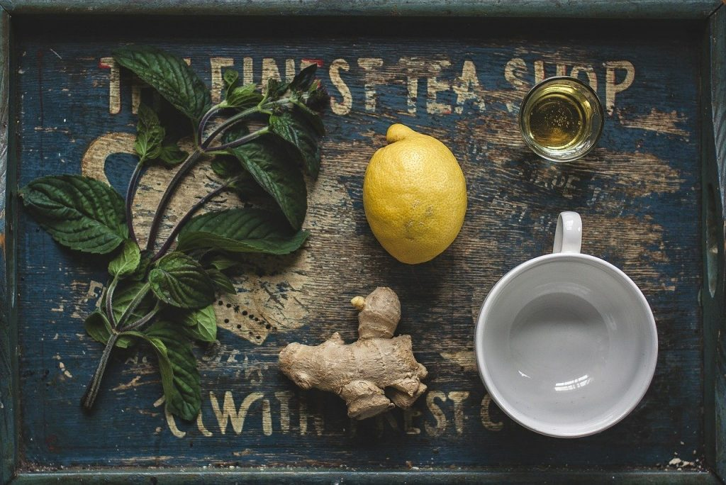 Lemon, ginger, honey, and some greens on a wooden tray.