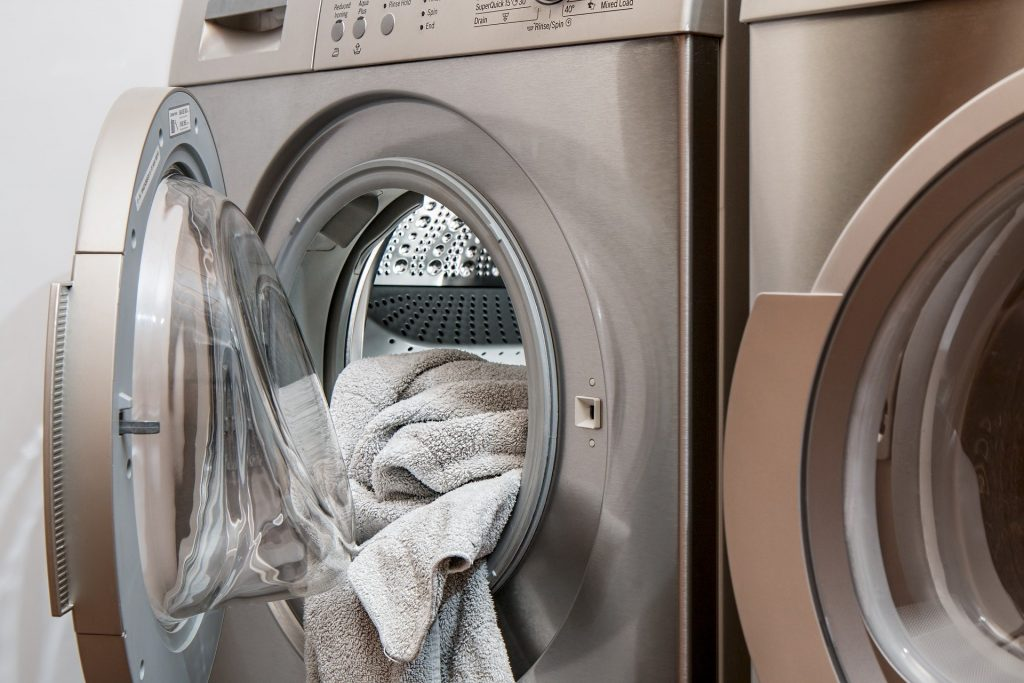 Washing machine with some laundry in it. Should you wash your workout clothes every time after gym session?
