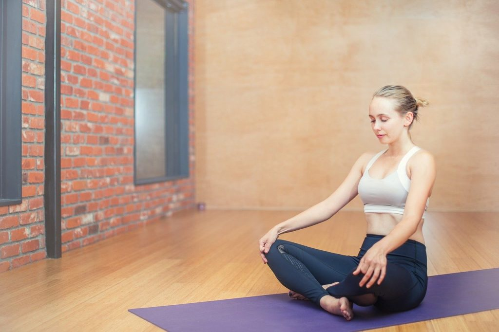 Woman meditating on a yoga mat.