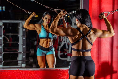 A woman bodybuilder using a pulley machine while facing mirror, lean protein foods help to build muscles.
