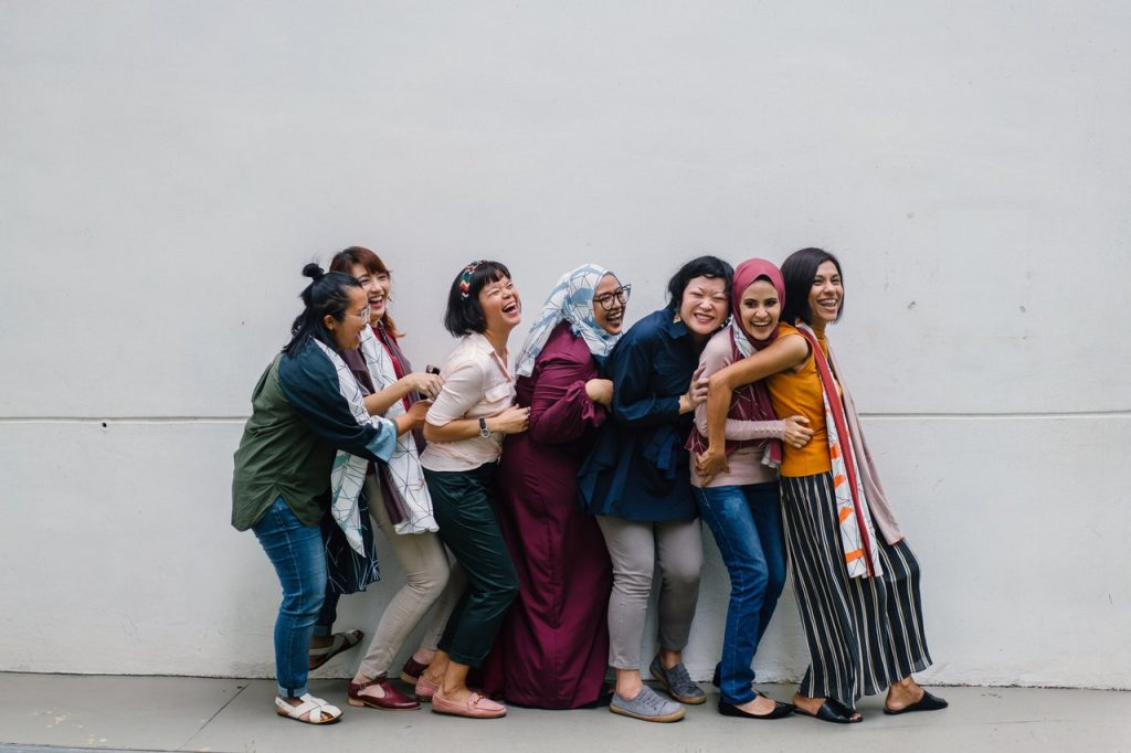 A group of women laughing while falling in line.