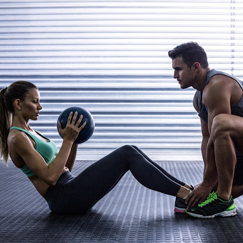 A woman doing sit-ups while holding a med ball and being assisted by her partner.