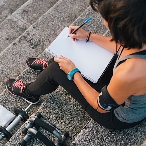 woman writing on blank notepad while sitting on urban stone stairs before exercises workout routine.
