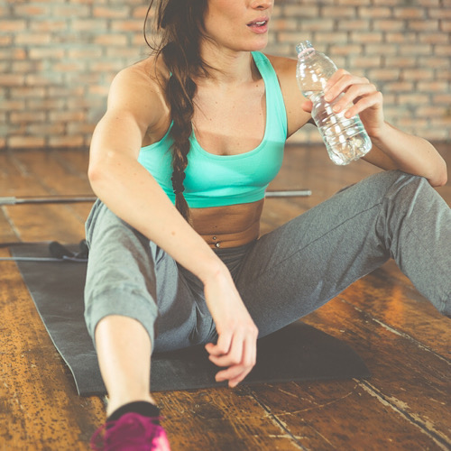A fit woman drinking water while resting with a dumbbells and a barbell at the back.
