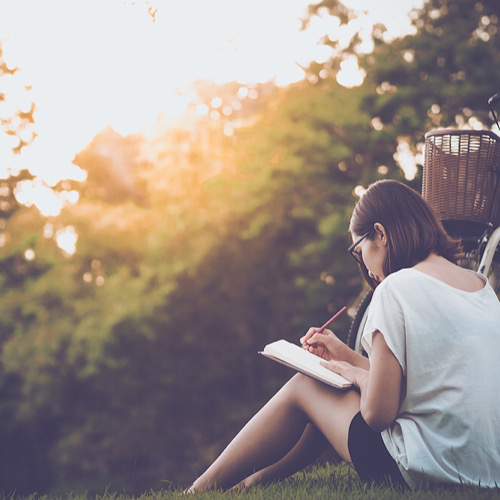 A woman writing on her diary while sitting on the grass.