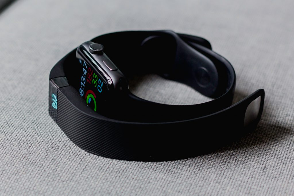 Close up and fitbit and apple watch.