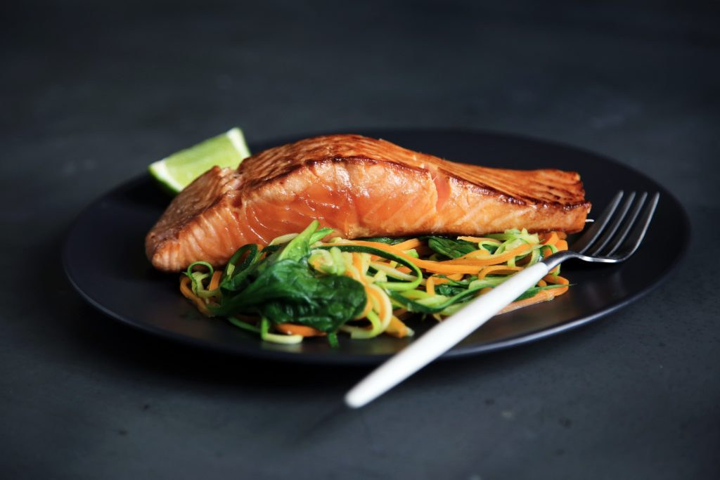 Salmon on plate with vegetables and a fork.