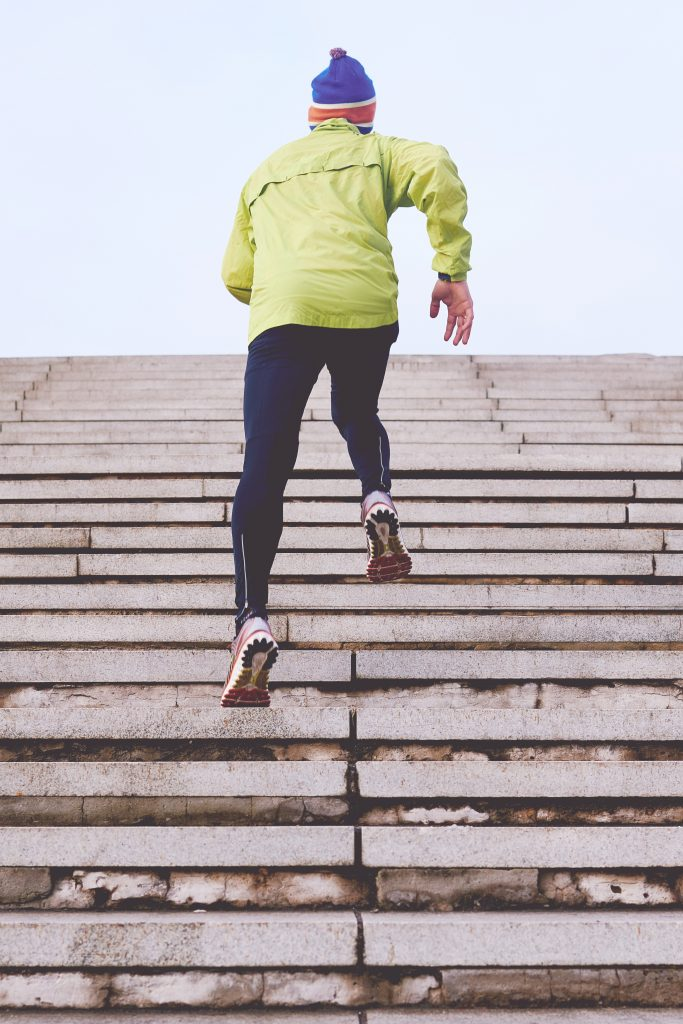 Man running up steps using appropriate running gear for men.