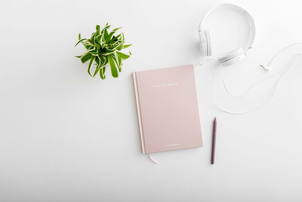 A diary on a white table top next to a pen, a potted plant, and headphones.