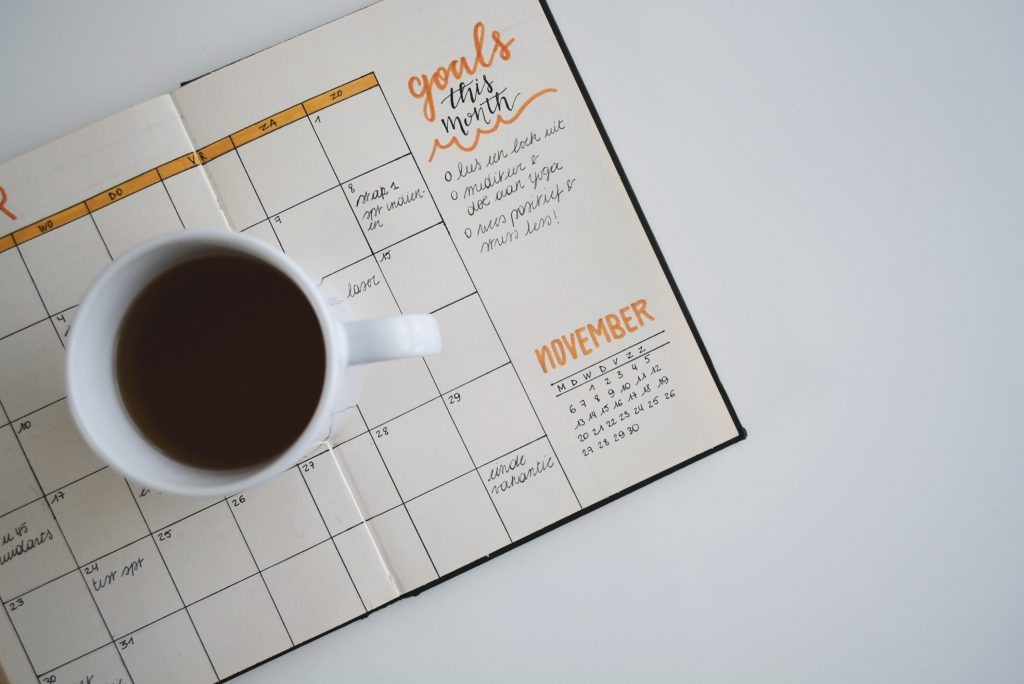 A calendar with notes about goals and a cup of coffee on top of it.