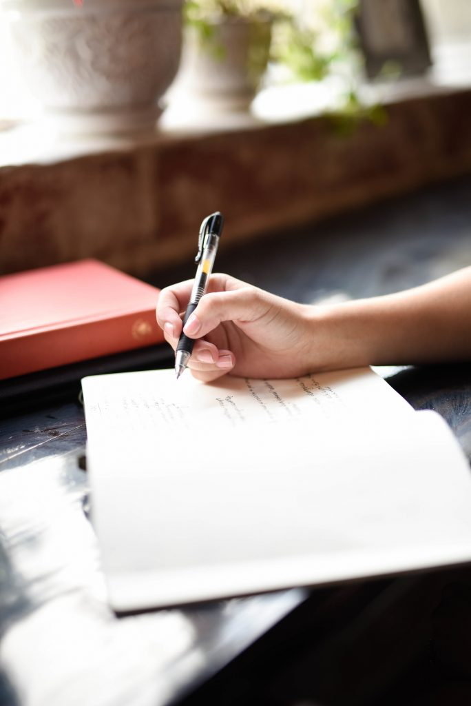 A pen and a journal on a table.