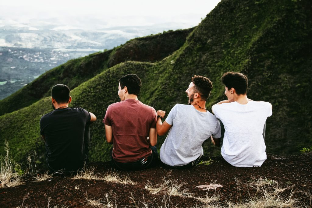 4 men laughing together while having a conversation on a hill. Is this part of life's purpose?