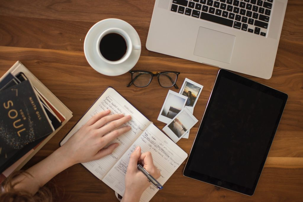 A woman writing on a notebook with her laptop, cup of coffee, reading glass, a tablet, and couple of books on a table figuring out what is life's purpose.