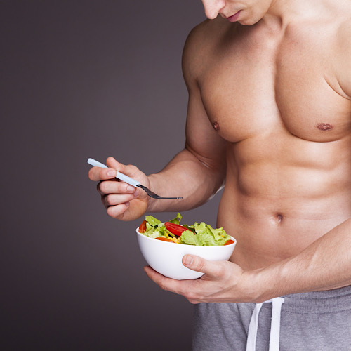 Athletic man holding a bowl of fresh salad on grey background.