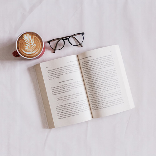 An open book, a cup of coffee and an eyeglass.