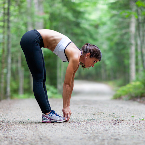 woman stretching in the woods on a dirt road before a run
