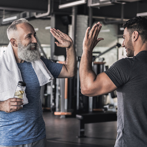 A senior and a young man in a gym doing high five.