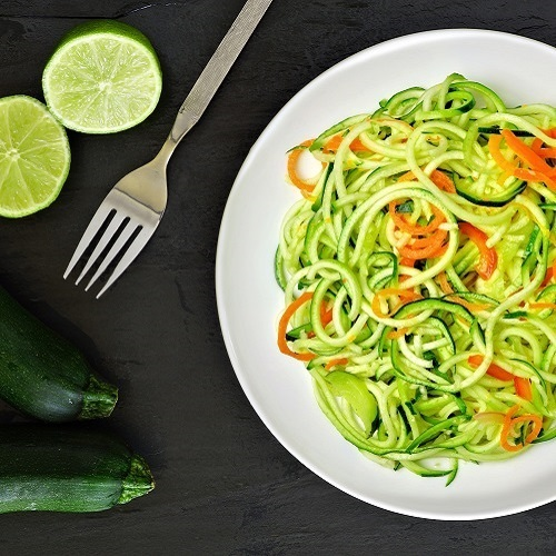 zucchini pasta in a plate, a fork and two slices of lime.
