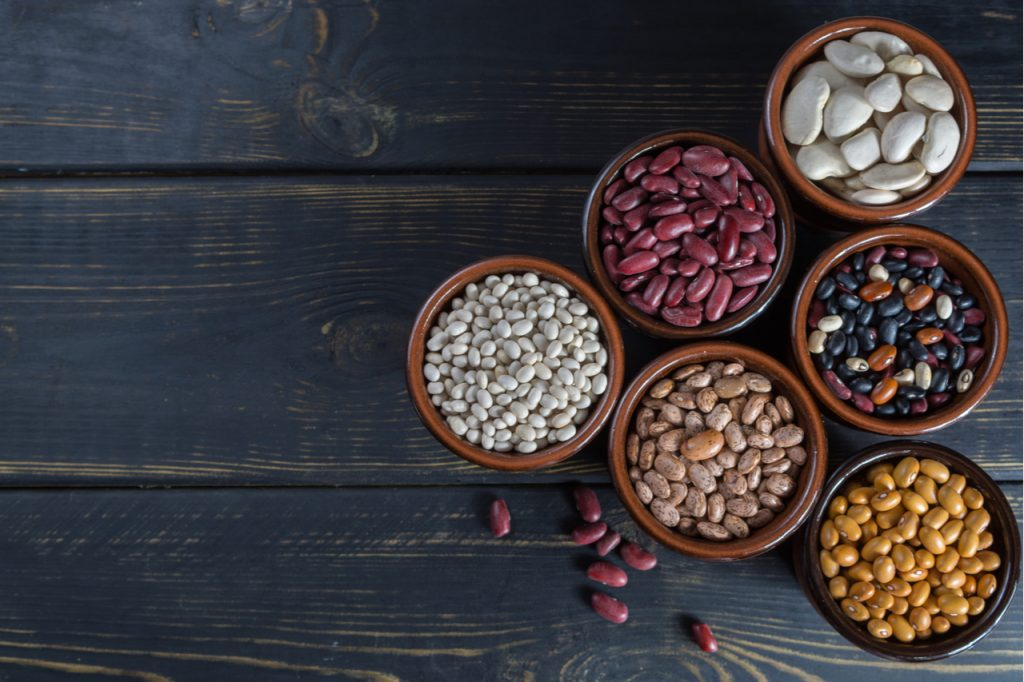 Assorted beans in bowls on a wooden table.