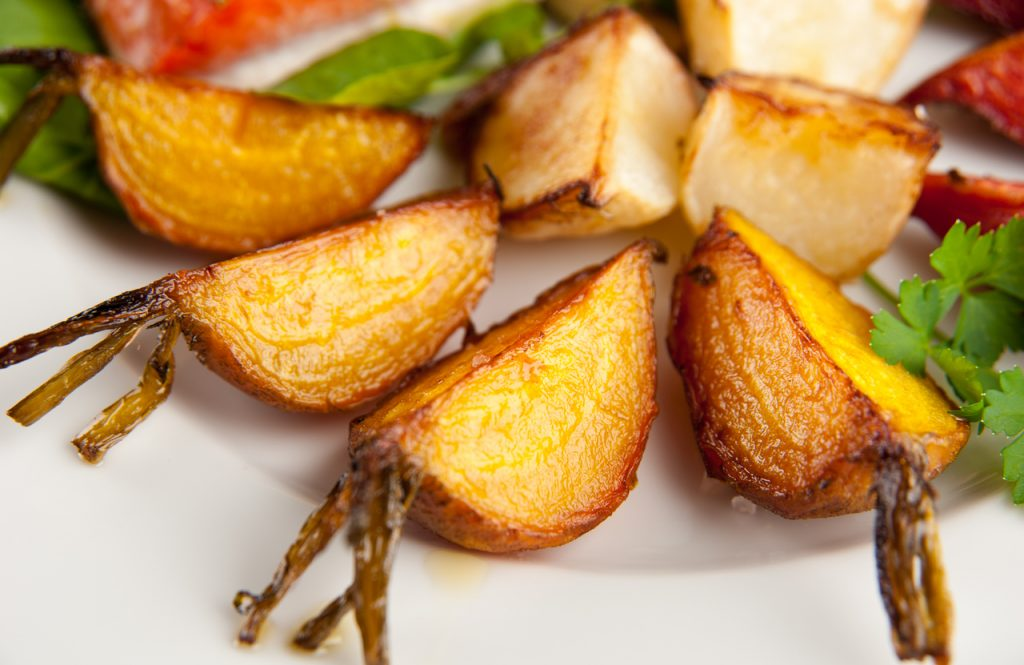 Carrot and turnip fries on a white plate.