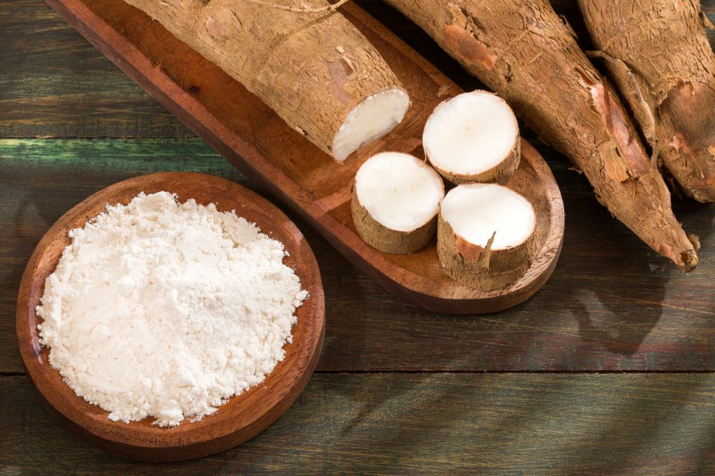 Cassava flour on a plate and some cassava roots on a wooden table.