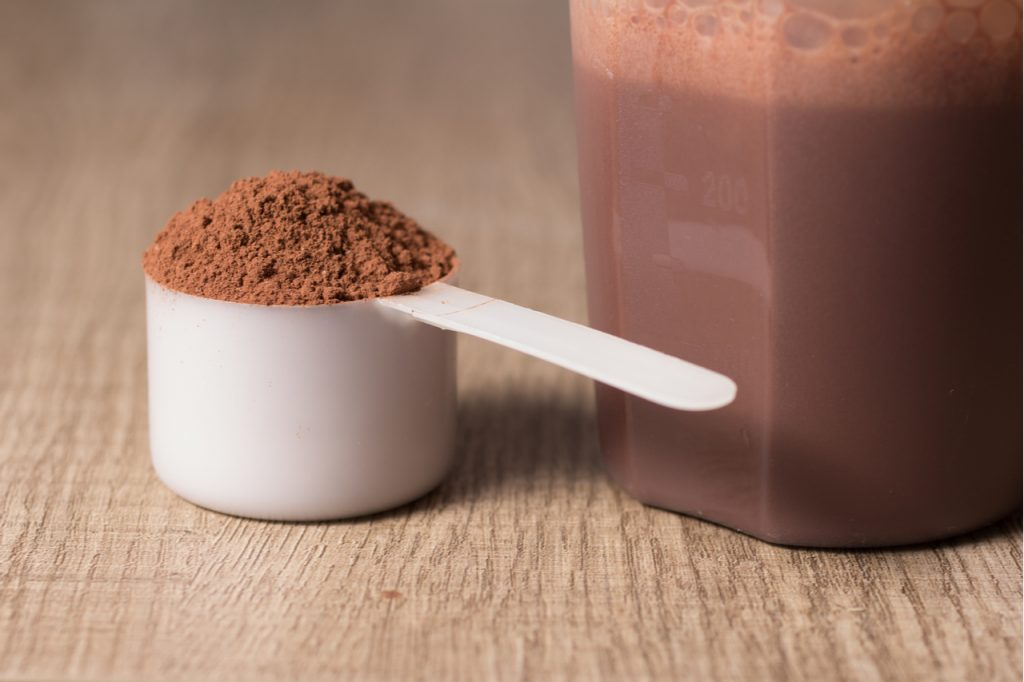 Chocolate protein powder in a measuring scoop next to a shaker bottle filled with protein shake.