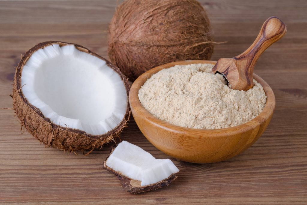 Coconut flour in a wooden bowl, next to a couple of coconuts.