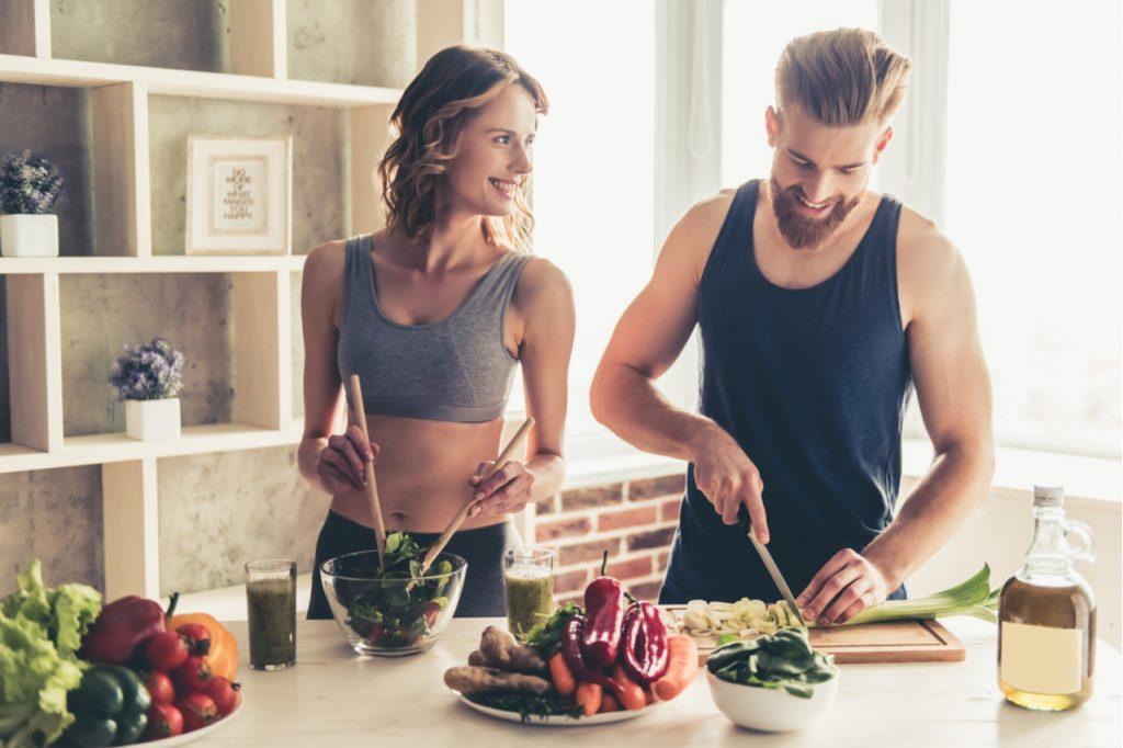 A man and woman enjoying cooking a vegetable dish together.