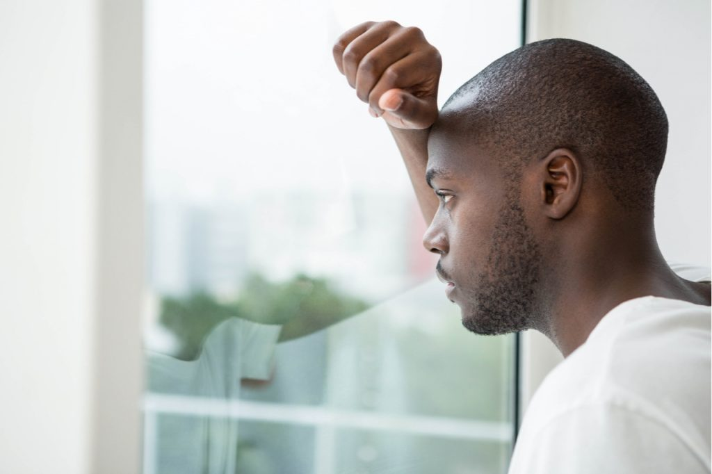 Man looking out the window showing signs of millennial depression.