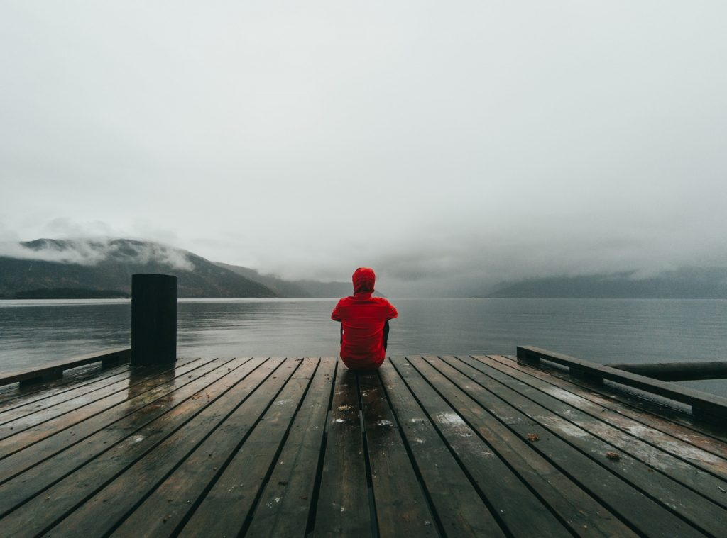 Lonely man sitting by the lake.