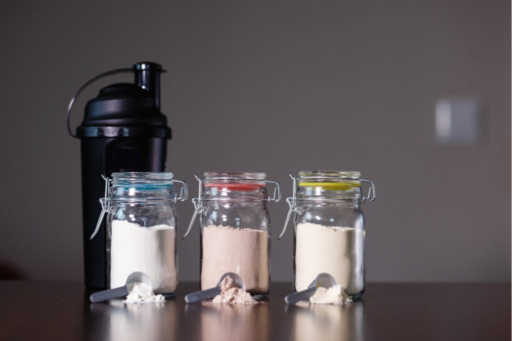 Three different protein powders in glass jars next to a shaker bottle.