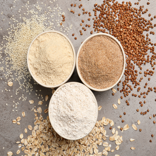 Top view of different types of flour in white bowls