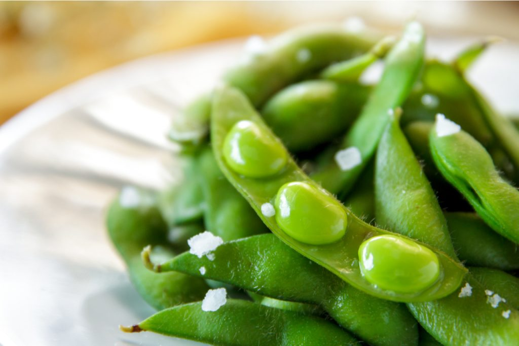 Japanese edamame beans on white plate.