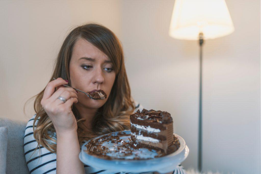Sad woman eating chocolate cake.