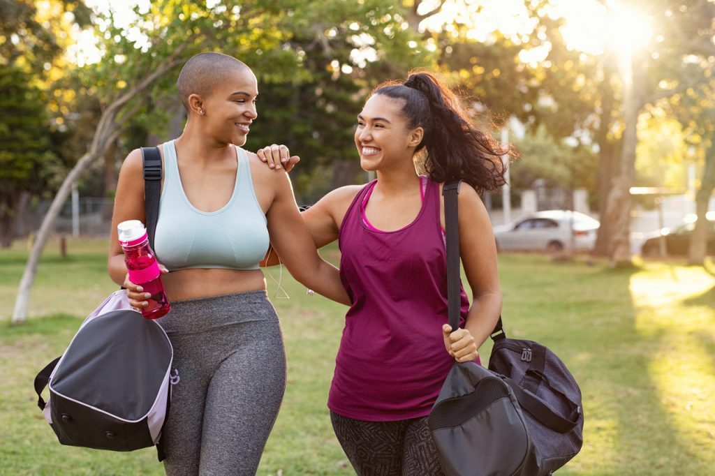 Friends looking happy while walking together, holding gym bags.