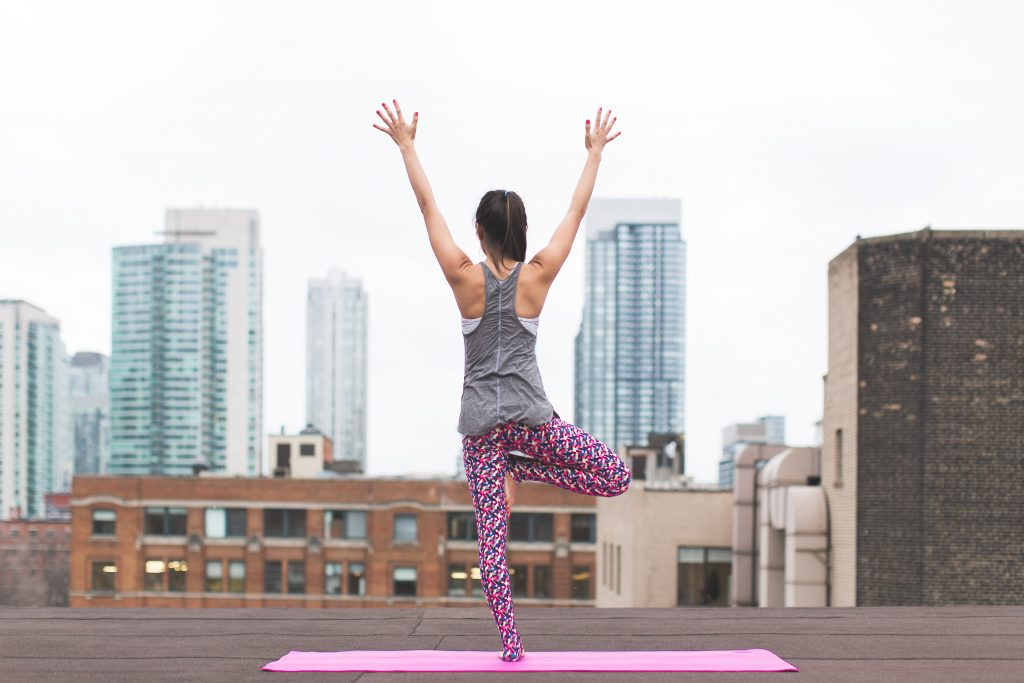 Fit woman exercising on a yoga mat on a rooftop.